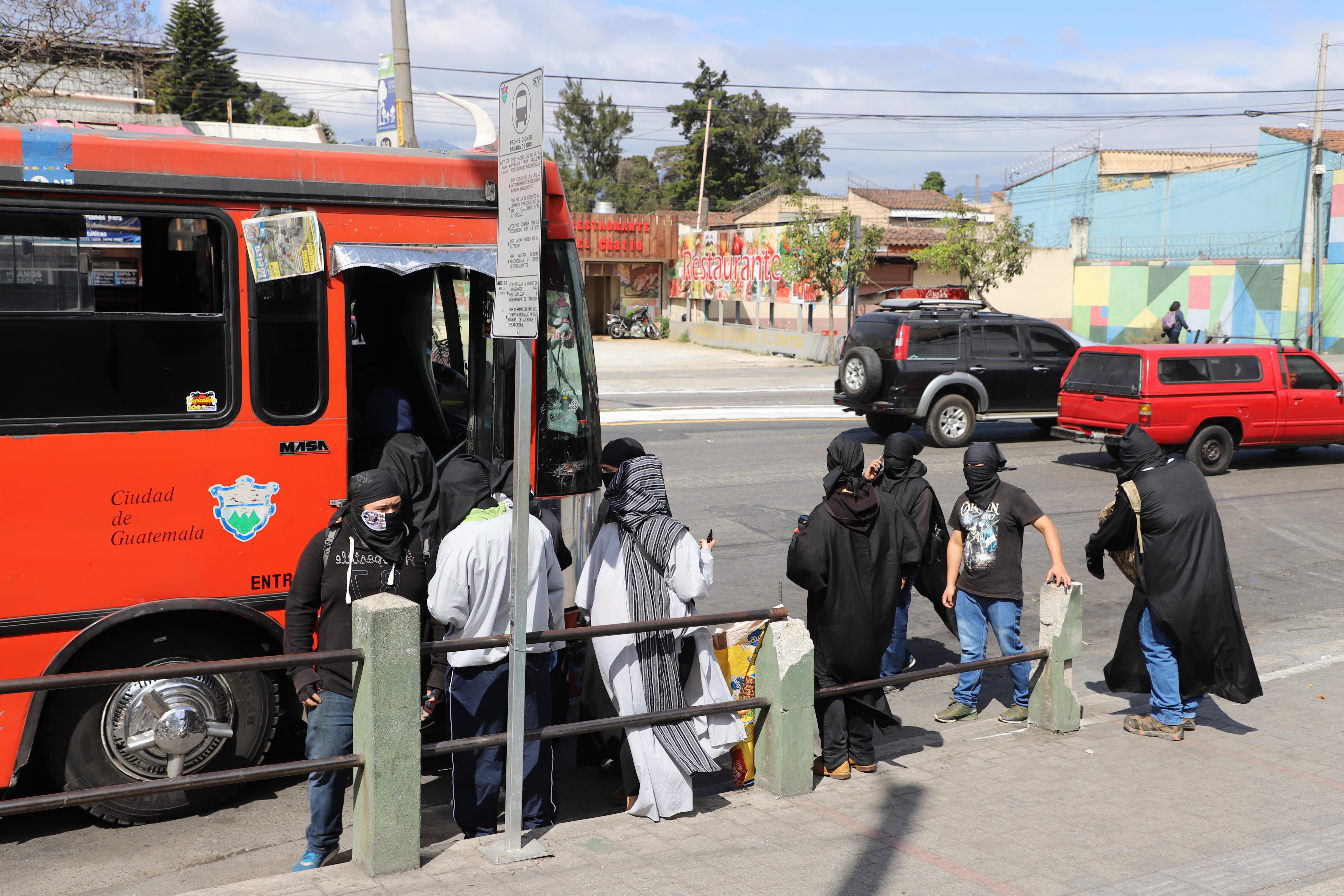 Encapuchados se retiran en buses tomados. Fotografía de Elio Morales.
