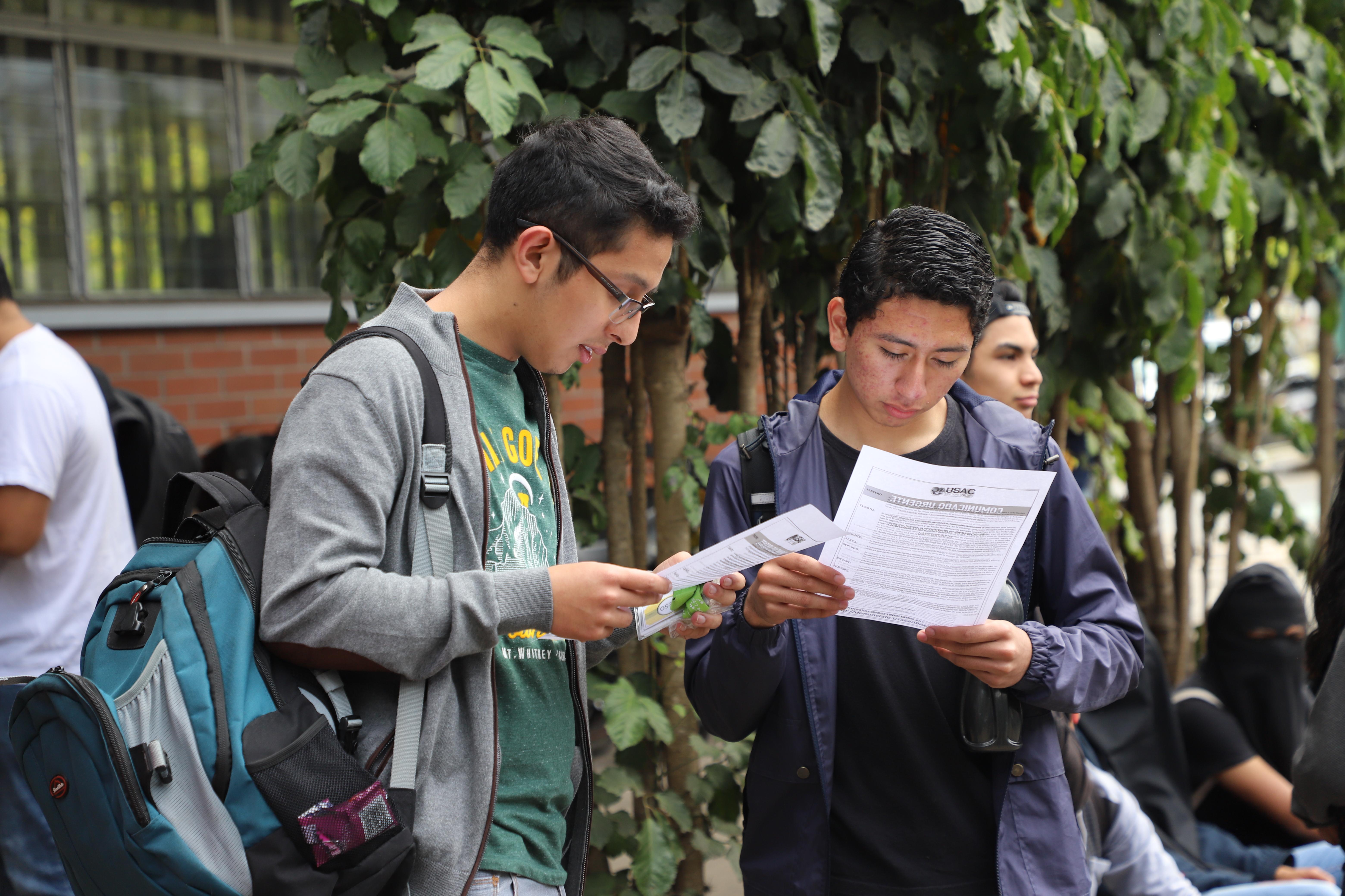 Estudiantes leen el comunicado que informa a la comunidad universitaria las prohibiciones para realizar bautizos. Fotografía Elio Morales.